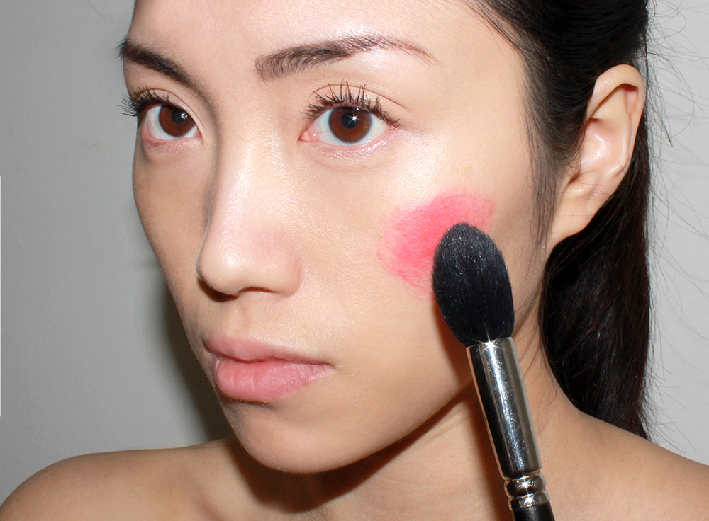 Blending cream blush on the cheeks